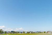 緑のグランドと住宅街と広い青空