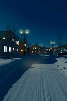 冬の夜の家並みと雪が積もった道路