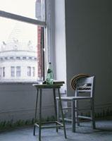 窓辺に置かれたテーブルとイスと帽子