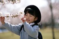 桜の木に触れる制服姿の女の子