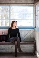 駅のホームで列車を待つ若い女性