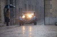 走る車と傘をさす人物 イタリア