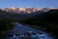 朝焼けに染まる白馬三山と松川