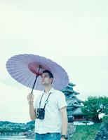 松本城と和傘を差す外国人の男性 8月 茅野郡 長野県