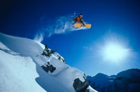 スノーボードでジャンプする人と雪山と日ざし