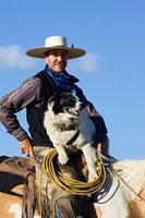 cowboy sitting on horseback with dog