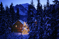 Snow covered log house and Christmas Tree, Post hotel, lake louise, Alberta, Canada