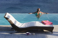 Sun lounger and woman in a swimming pool