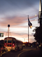 NICARAGUA, Grenada, traffic driving through downtown with the Nicaraguan flag in the distance