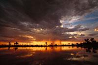 泉の上の日没りと嵐雲