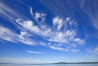 White cirrus clouds floating in clear blue sky over Bay of F