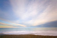 Gentle surf rolling on sandy beach at sunrise in winter�A We