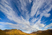 Cirrus and cumulus clouds above Alaska Range and fall tundra