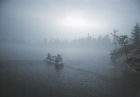 雨の中カヌーを漕ぐ人