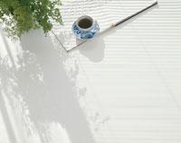 白いテーブルの上の観葉植物と本とコーヒー
