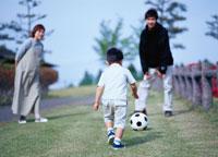 サッカーをする3人の日本人の親子