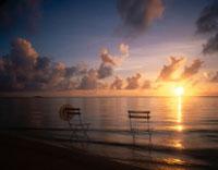 夕暮れの海辺に椅子と帽子 宮古島 沖縄県 01673004765| 写真素材・ストックフォト・画像・イラスト素材|アマナイメージズ