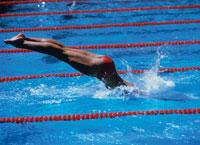 水しぶきを上げプールに飛びこむ女性