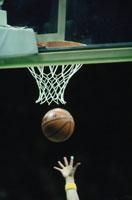 バスケットのゴールネットとシュートする手