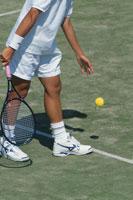 テニスのサーブをする人物