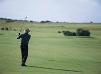 ゴルフのアイアンショットをする人物の後姿