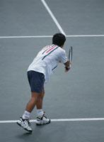 テニスのサーブをする人物の後姿