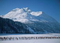 クロスカントリーをする人物と雪山