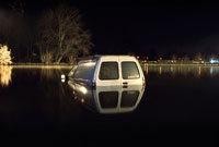 Van on flooded road, at night