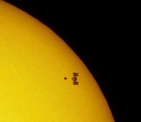 ISS and Atlantis against the Sun