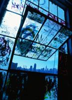 廃墟の窓ガラスの落書きとマンハッタンビル群