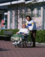 車椅子の中高年男性と付き添う女性
