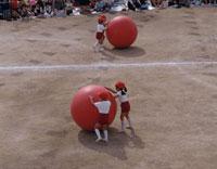 運動化にて大玉送りの競技をする日本人小学生