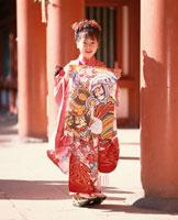 朱門で武者凧を持つ振袖の女の子
