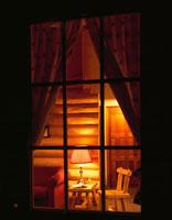 夜のログハウスの窓越の室内 ジャスパー カナダ