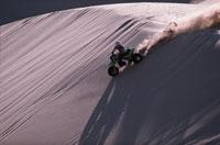 砂の斜面をバイクで走る人 アメリカ