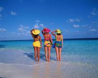 波打ち際に並ぶ3人の外国人女性 夏