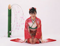 餅花の前に座る振り袖姿の日本人女性