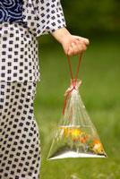 金魚の袋を持つ浴衣の子供の手
