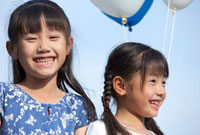 青空と風船を持つ姉妹