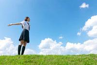 空に向かって両手を広げる女子高校生