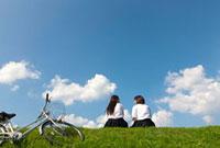 土手に座っておしゃべりする二人の女子高校生