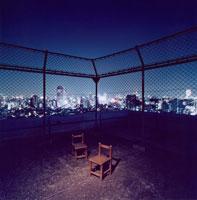 都市の夜景と屋上の子供の椅子