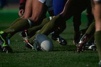 ラグビーをする人物たちの足とボール