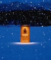 雪の中に立つドアとリース