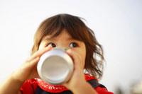 缶ジュースを飲む女の子
