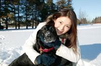 雪の上で犬を抱く日本人女性 02129010558| 写真素材・ストックフォト・画像・イラスト素材|アマナイメージズ