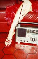 赤いソファに座る女性の手足とラジオ