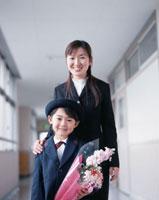 学校の廊下にて花束を抱えた日本人小学生と女性