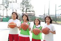 校庭に立つバスケット部の中学生