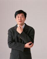 腕を抱える日本人中高年ビジネスマン